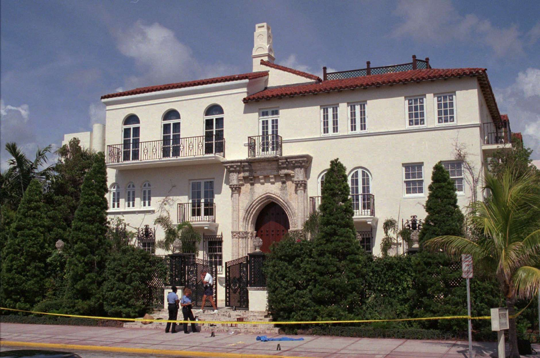 The mansion of Italian fashion designer Gianni Versace is flanked with police and small flags indicating evidence in the shooting death of the famed designer Tuesday, July 15, 1997. The 50-year-old Versace was shot on the steps of his Miami Beach home by an unknown suspect, described as being a male in his 20's.  (AP Photo/Gregory Smith)