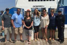 A group of researchers and guests pose for a photo aboard the OCEARCH. (WTOP/Michelle Basch)