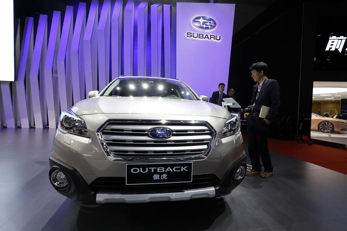 A man looks at the Subaru Outback SUV   during the Auto Shanghai 2017 show at the National Exhibition and Convention Center in Shanghai, China, Thursday, April 20, 2017.  Models on display at Auto Shanghai 2017, the global industry's biggest marketing event of the year, reflect the conflict between Beijing's ambitions to promote environmentally friendly propulsion and Chinese consumers' love of hulking, fuel-hungry SUVs.  (AP Photo/Ng Han Guan)