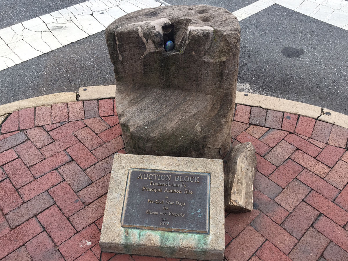 The old auction block -- concrete and not much taller than a fire hydrant -- is one of Fredericksburg's reminders of its history in the slave trade. The city council acted Tuesday to allow city officials to develop recommendations about what to do with the auction block. (WTOP/Dennis Foley)