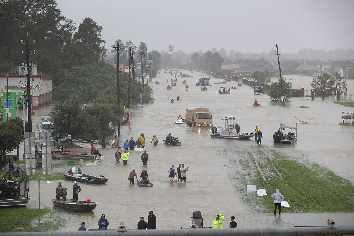 HOUSTON, TX - AUGUST 28:  People walk down a flooded street as they evacuate their homes after the area was inundated with flooding from Hurricane Harvey on August 28, 2017 in Houston, Texas. Harvey, which made landfall north of Corpus Christi late Friday evening, is expected to dump upwards to 40 inches of rain in Texas over the next couple of days.  (Photo by Joe Raedle/Getty Images)