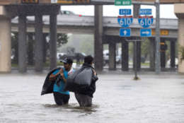 HOUSTON, TX - AUGUST 28:  Local apartment residents cross high water on North Braeswood Blvd to escape the flooding from Hurricane Harvey August 28, 2017 in Houston, Texas. Harvey, which made landfall north of Corpus Christi late Friday evening, is expected to dump upwards to 40 inches of rain in areas of Texas over the next couple of days.  (Photo by Erich Schlegel/Getty Images)