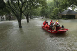 A Coast Guard rescue team evacuates people from a neighborhood inundated by floodwaters from Tropical Storm Harvey on Monday, Aug. 28, 2017, in Houston, Texas. (AP Photo/Charlie Riedel)