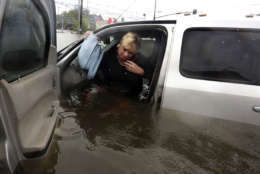 Rhonda Worthington talks on her cell phone with a 911 dispatcher as he gets out of her car after her vehicle become stalled in rising floodwaters from Tropical Storm Harvey in Houston, Texas, Monday, Aug. 28, 2017. Worthington said she thought the water was low enough to drive through before the vehicle started to float away. (AP Photo/LM Otero)