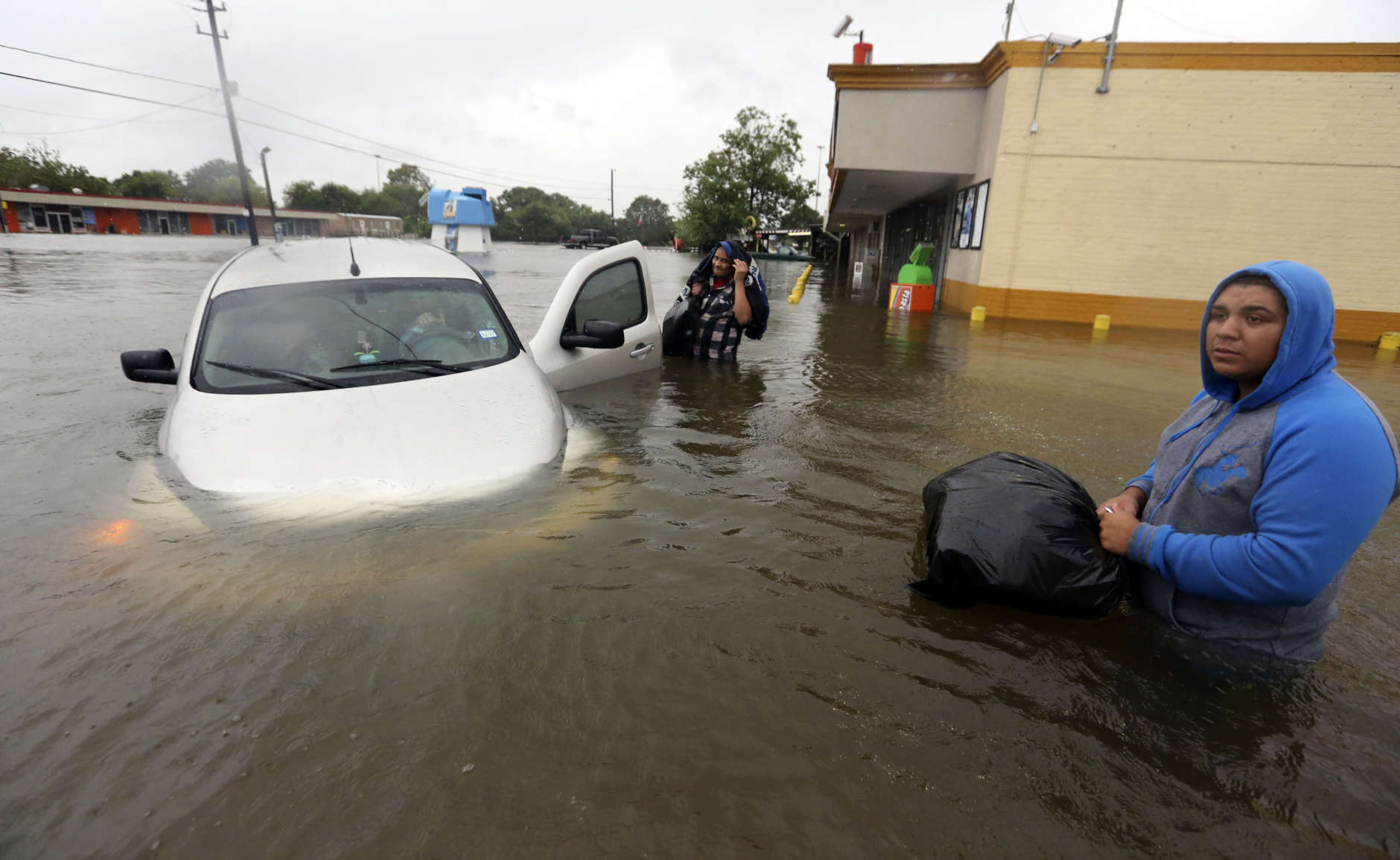 Conception Casa, center, and his friend Jose Martinez, right, check on Rhonda Worthington after her car become stuck in rising floodwaters from Tropical Storm Harvey in Houston, Texas, Monday, Aug. 28, 2017. The two men were evacuating their home that had become flooded when they encountered Worthington's car floating off the road. (AP Photo/LM Otero)