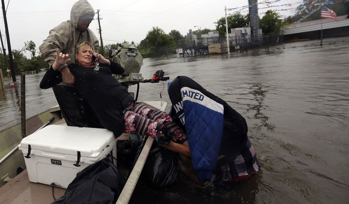 Rhonda Worthington is lifted into a boat while on her cell phone with a 911 dispatcher after her car become stuck in rising floodwaters from Tropical Storm Harvey in Houston, Texas, Monday, Aug. 28, 2017. (AP Photo/LM Otero)