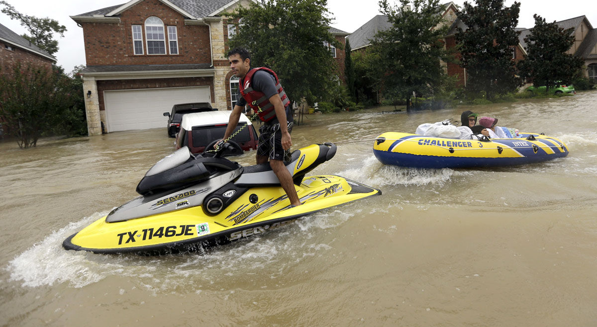 Flood victims are towed to safety by a jet ski as floodwaters from Tropical Storm Harvey rise Monday, Aug. 28, 2017, in Spring, Texas. (AP Photo/David J. Phillip)