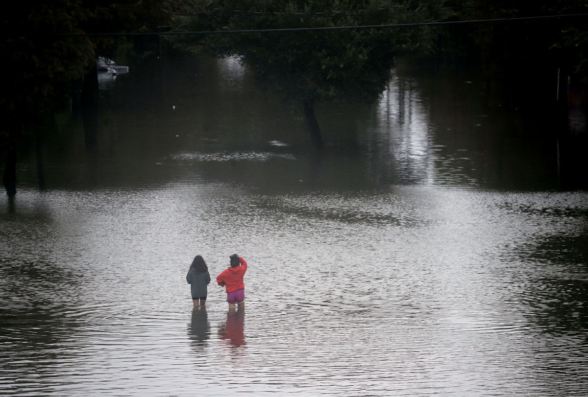 People walk through floodwaters from Tropical Storm Harvey on Sunday, Aug. 27, 2017, in Houston. (AP Photo/Charlie Riedel)