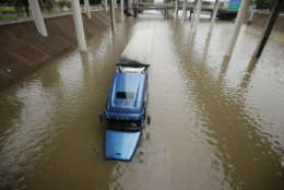 A truck is submerged on a freeway flooded by Tropical Storm Harvey on Sunday, Aug. 27, 2017, near downtown Houston. The remnants of Hurricane Harvey sent devastating floods pouring into Houston Sunday as rising water chased thousands of people to rooftops or higher ground. (AP Photo/Charlie Riedel)