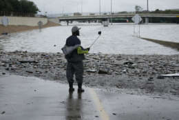 A man takes photos of a freeway flooded by Tropical Storm Harvey on Sunday, Aug. 27, 2017, near downtown Houston, Texas. (AP Photo/Charlie Riedel)