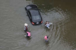 Residents wade through floodwaters as they evacuate their homes near the Addicks Reservoir as floodwaters from Tropical Storm Harvey rise Tuesday, Aug. 29, 2017, in Houston. (AP Photo/David J. Phillip)