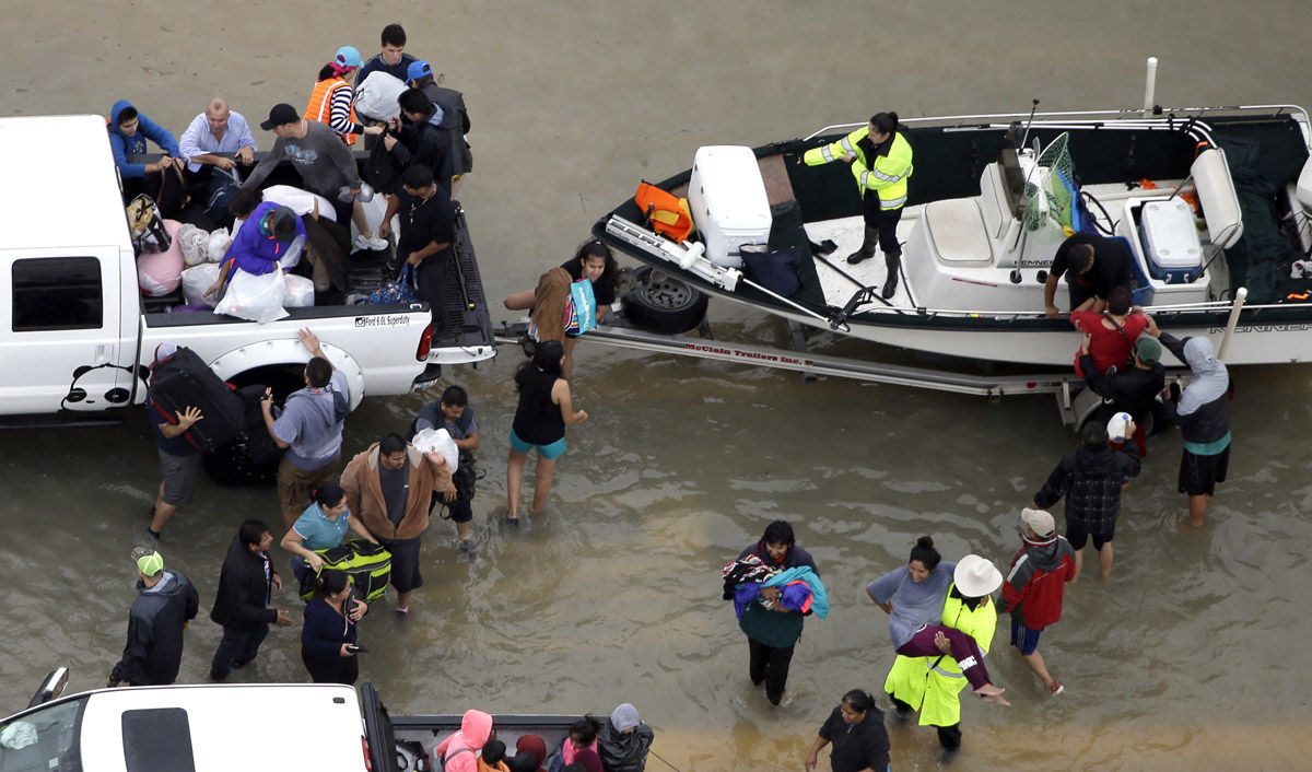 Evacuees are helped as floodwaters from Tropical Storm Harvey rise Tuesday, Aug. 29, 2017, in Houston. (AP Photo/David J. Phillip)