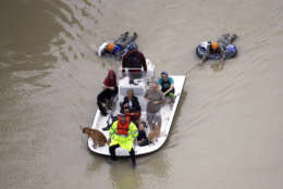 Evacuees make their way though floodwaters near the Addicks Reservoir as floodwaters from Tropical Storm Harvey rise Tuesday, Aug. 29, 2017, in Houston. (AP Photo/David J. Phillip)