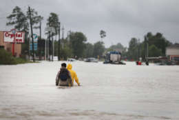 HOUSTON, TX - AUGUST 29:  People make their way out of a flooded neighborhood after it was inundated with rain water following Hurricane Harvey on August 29, 2017 in Houston, Texas. Harvey, which made landfall north of Corpus Christi August 25, has dumped nearly 50 inches of rain in and around areas Houston.  (Photo by Scott Olson/Getty Images)