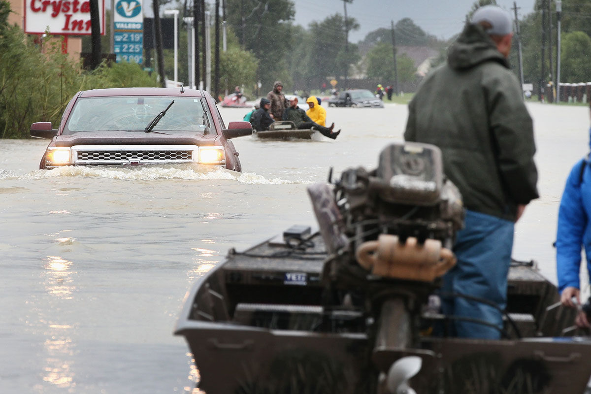 HOUSTON, TX - AUGUST 29:  Rescue workers and volunteers help residents make their way out of a flooded neighborhood after it was inundated with rain water following Hurricane Harvey on August 29, 2017 in Houston, Texas. Harvey, which made landfall north of Corpus Christi August 25, has dumped nearly 50 inches of rain in and around areas Houston.  (Photo by Scott Olson/Getty Images)
