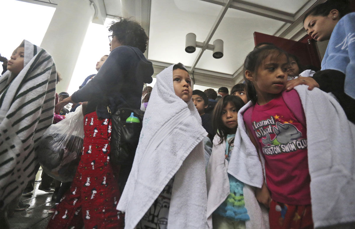 Children and adults wait to get into the George R. Brown Convention Center after evacuating during Tropical Storm Harvey in Houston, on Tuesday, Aug. 29, 2017. (AP Photo/LM Otero)