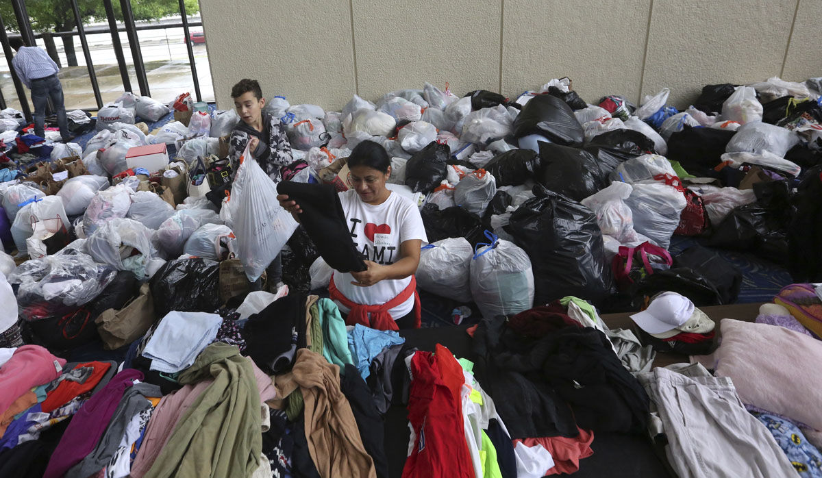 Volunteers Brenda Tcoc, right, and Hugo Wilson help sort bags of donated clothes for victims of the flooding from Tropical Storm Harvey after a shelter opened at the Lakewood Church in Houston, Texas, Tuesday, Aug. 29, 2017. (AP Photo/LM Otero)
