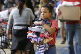 Volunteer Asuleni Santiago, 11, carries donated clothes for victims of the flooding from Tropical Storm Harvey at a shelter opened at the Lakewood Church in Houston, Texas, Tuesday, Aug. 29, 2017. (AP Photo/LM Otero)