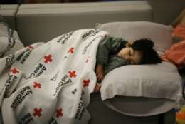 ADDS NAME OF BOY - Malachia Medrano, 2, sleeps at the George R. Brown Convention Center that has been set up as a shelter for evacuees escaping the floodwaters from Tropical Storm Harvey in Houston, Texas, Tuesday, Aug. 29, 2017. (AP Photo/LM Otero)