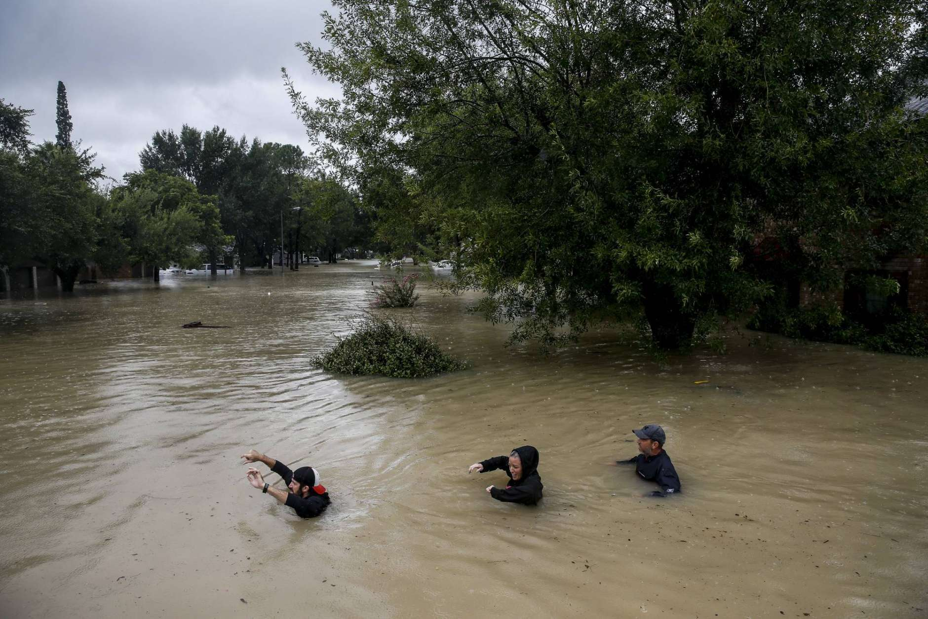 People wade through chest deep water down Pine Cliff Drive as Addicks Reservoir nears capacity due to near constant rain from Tropical Storm Harvey, Tuesday, Aug. 29, 2017 in Houston. (Michael Ciaglo/Houston Chronicle via AP)