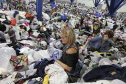 Kathryn Loder sorts donated clothing at George R. Brown Convention Center in Houston as Tropical Storm Harvey inches its way through the area on Tuesday, Aug. 29, 2017. ( Elizabeth Conley/Houston Chronicle via AP)