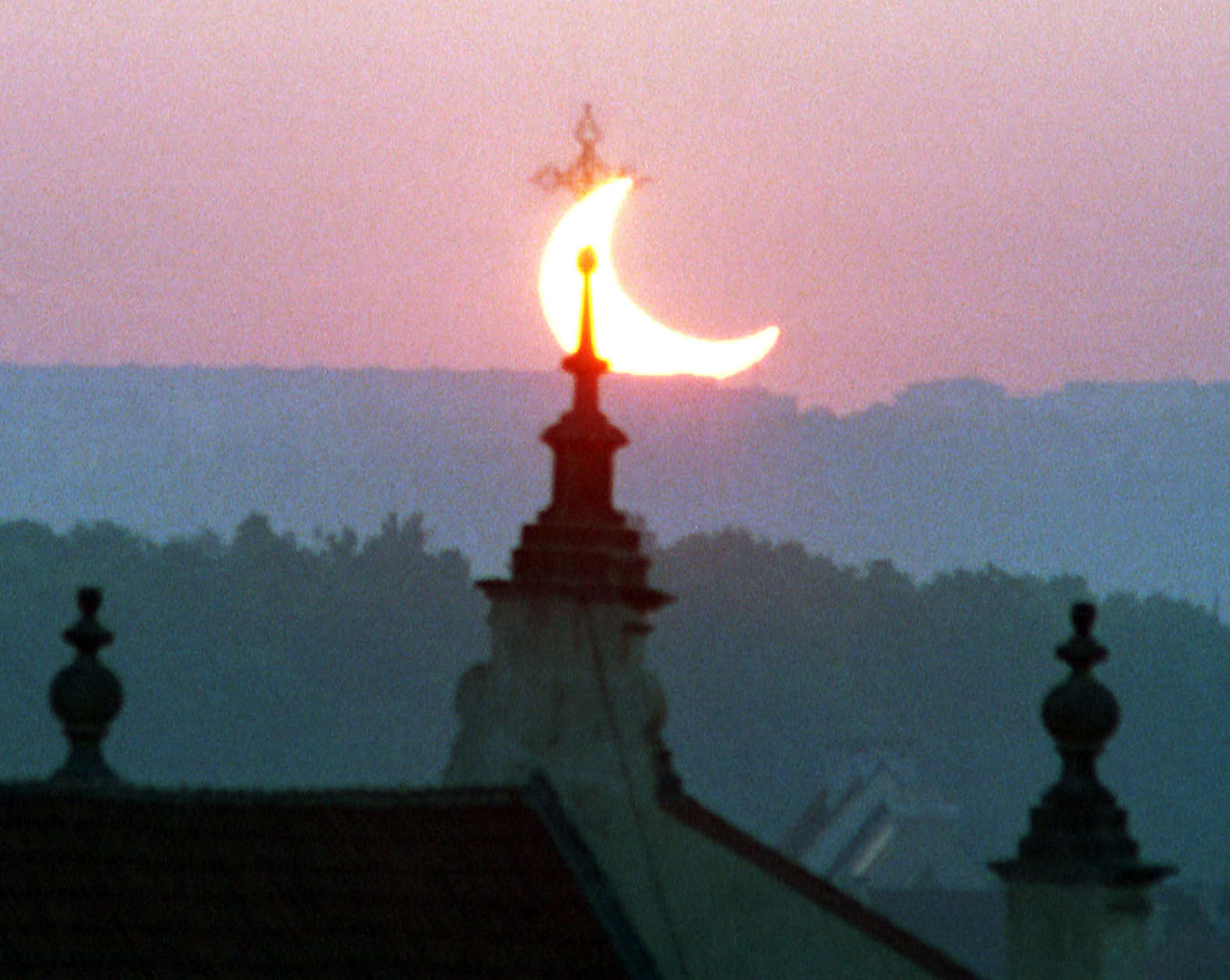 The sun is seen behind a tower of a Prague's church during a partial solar eclipse at dawn on Saturday, May 31, 2003. (AP Photo/CTK, Ivan Vetvicka)