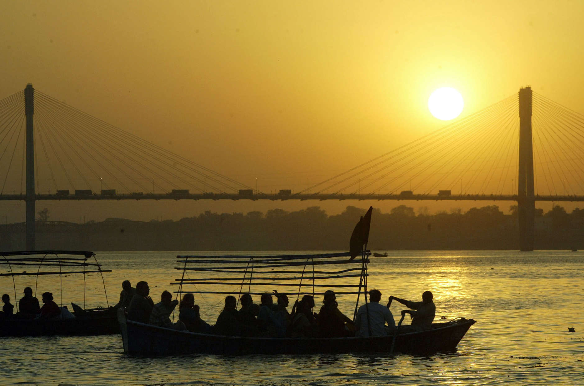 Hindu devotees row back to the shore after taking a bath in the River Ganges during the solar eclipse, in Allahabad, India, Wednesday, March 29, 2006. Hindus pray during the solar eclipse to ward off evil. (AP Photo/Rajesh Kumar Singh)