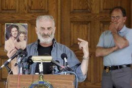 Ruby Ridge survivor Randy Weaver holds a photo of his wife Vicki, and 10-month-old daughter Elishiba as Ed Brown, back right, listens in Plainfield, N.H., Monday, June 18, 2007. Weaver's wife and child were killed in 1992 during a raid by federal agents. Ed and Elaine Brown have been convicted of tax evasion and have been holed up in their home refusing to pay back taxes. (AP Photo/Jim Cole)