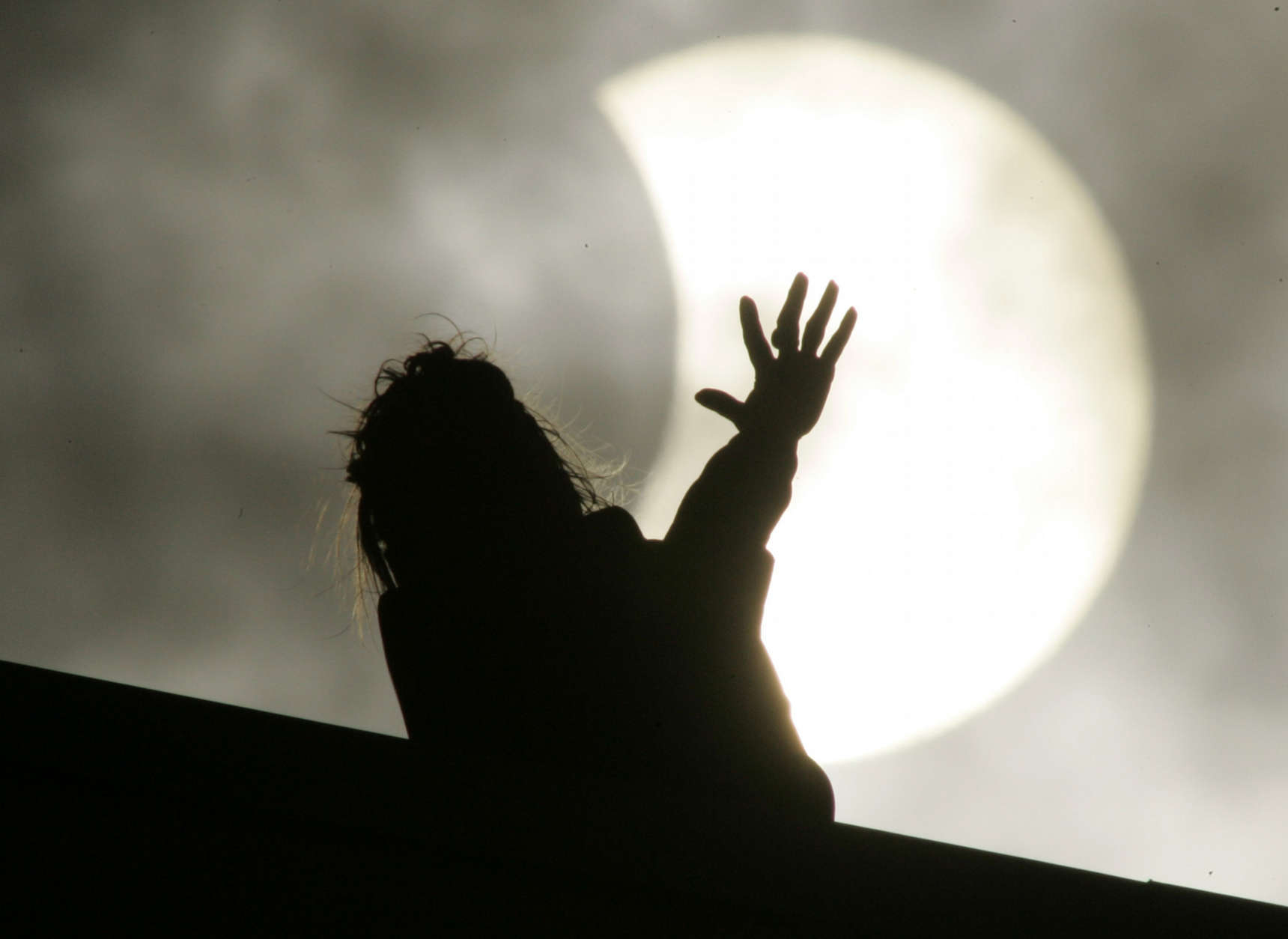 A woman looks at the moon partly covering the sun, during a partial solar eclipse, in St.Petersburg, Russia, Friday, Aug. 1, 2008. (AP Photo/Dmitry Lovetsky)