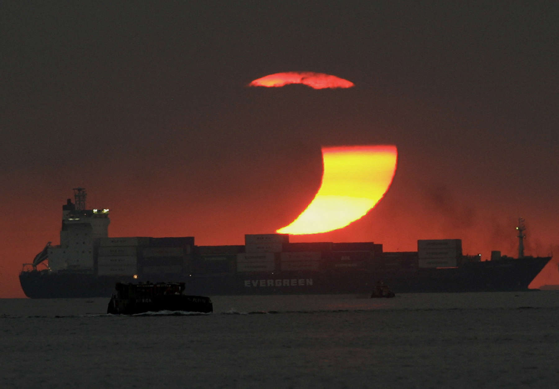 The moon cast a shadow at the sun blocking it partially in a partial solar eclipse as it sets on Monday Jan. 26, 2009 at Manila's bay, Philippines. (AP Photo/Aaron Favila)
