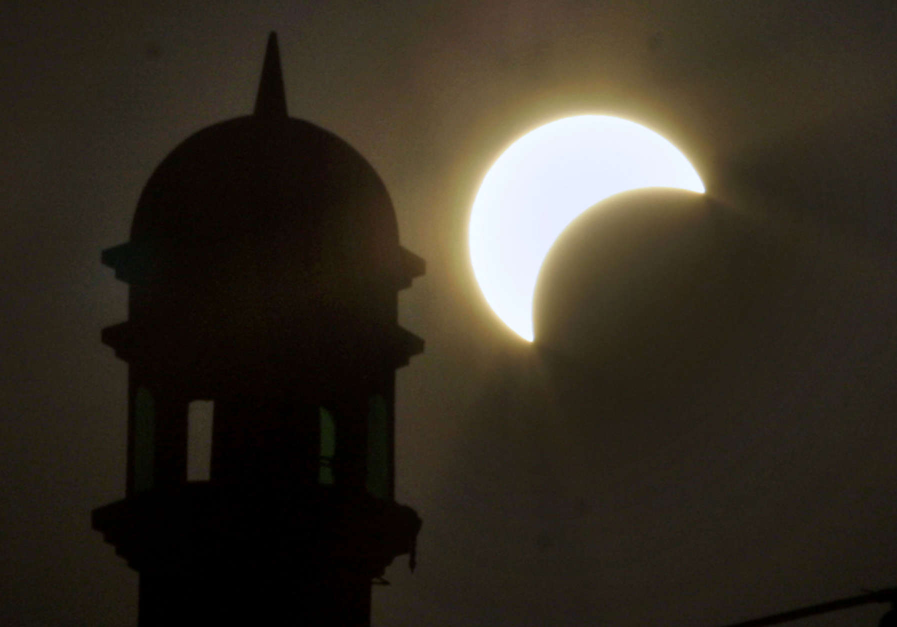 A partial solar eclipse is seen near the minaret of a mosque in Rawalpindi, Pakistan on Wednesday, July 22, 2009. The longest solar eclipse of the 21st century pitched a swath of Asia from India to China into near darkness Wednesday as millions gathered to watch the phenomenon. (AP Photo/Anjum Naveed)