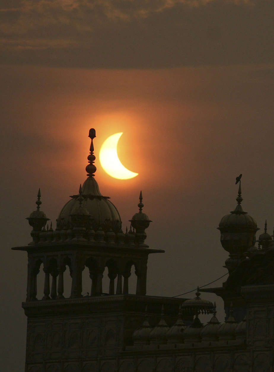 A partial solar eclipse is seen behind the Golden Temple, a Sikhs holiest shrine, in Amritsar, India, Wednesday, July 22, 2009. Millions of Asians turned their eyes skyward Wednesday as dawn suddenly turned to darkness across the continent in the longest total solar eclipse this century will see. Millions of others, seeing the rare event as a bad omen, shuttered themselves indoors. (AP Photo/Altaf Qadri)