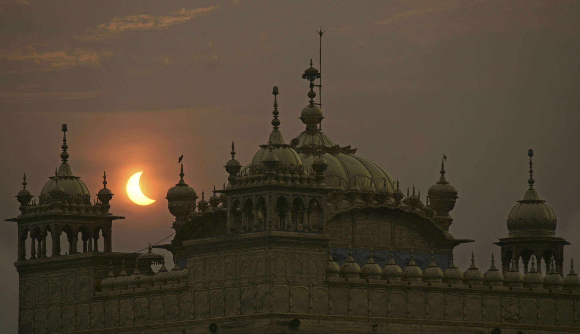 A partial solar eclipse is seen behind the Golden Temple, Sikhs holiest shrine, in Amritsar, India, Wednesday, July 22, 2009. Millions of Asians turned their eyes skyward Wednesday as dawn suddenly turned to darkness across the continent in the longest total solar eclipse this century will see. Millions of others, seeing the rare event as a bad omen, shuttered themselves indoors. (AP Photo/Altaf Qadri)
