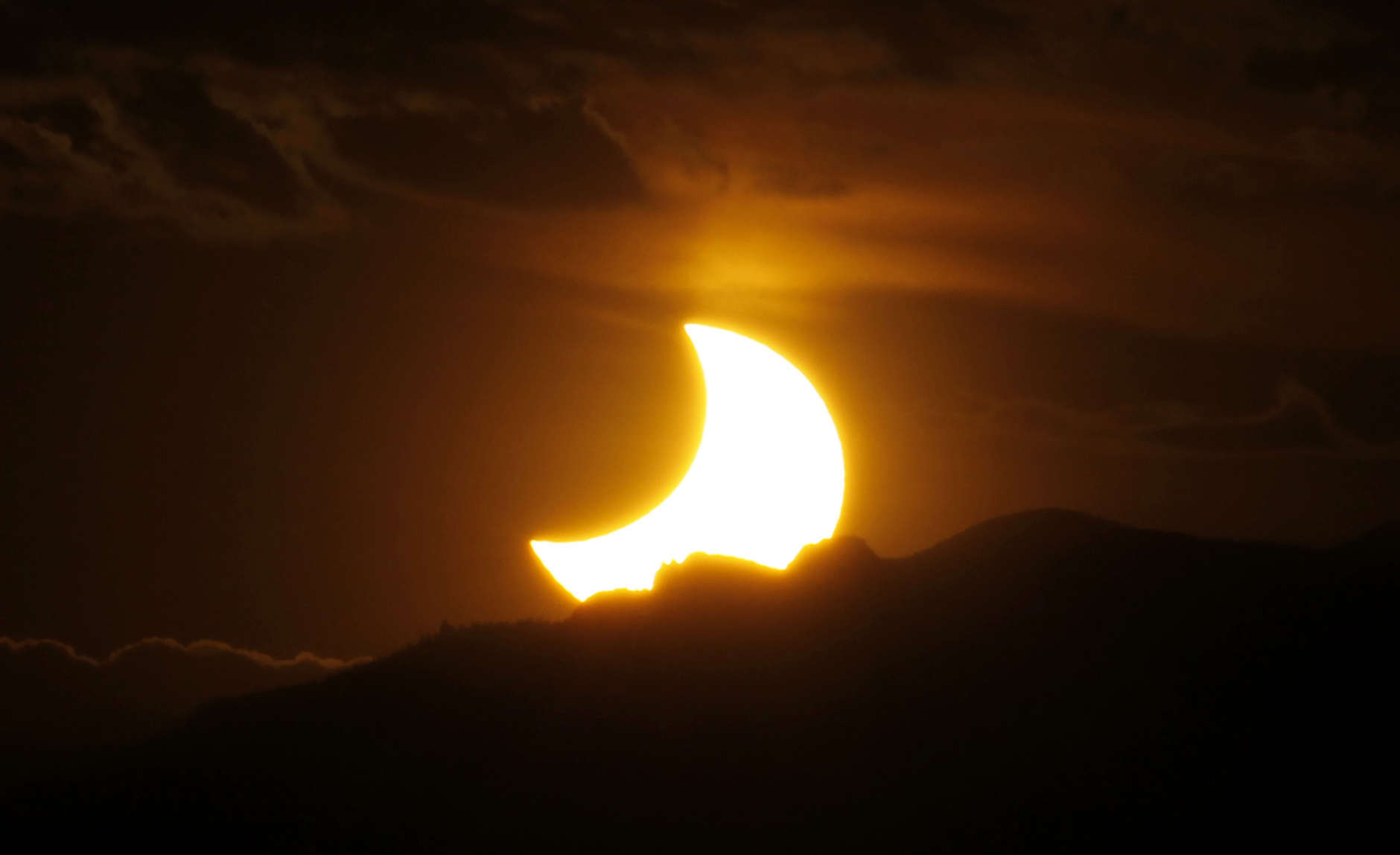 FILE - In this May 20, 2012, file photo, the annular solar eclipse is seen as the sun sets behind the Rocky Mountains from downtown Denver. Destinations are hosting festivals, hotels are selling out and travelers are planning trips for the total solar eclipse that will be visible coast to coast on Aug. 21, 2017. A narrow path of the United States 60 to 70 miles wide from Oregon to South Carolina will experience total darkness, also known as totality. (AP Photo/David Zalubowski, File)