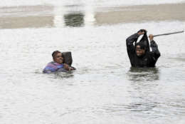 A man and woman try to navigate through floodwaters from Tropical Storm Harvey Sunday, Aug. 27, 2017, in Houston, Texas. (AP Photo/David J. Phillip)