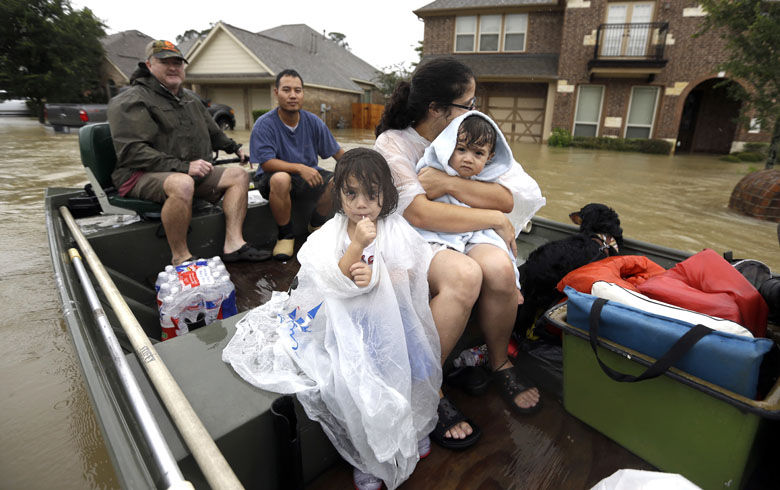 A family is evacuated from their home as floodwaters from Tropical Storm Harvey rise Monday, Aug. 28, 2017, in Spring, Texas. (AP Photo/David J. Phillip)