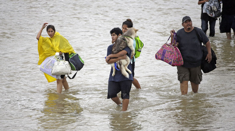 Evacuees wade down Tidwell Rd. after being evacuated from their homes as floodwaters from Tropical Storm Harvey rise Monday, Aug. 28, 2017, in Houston. (AP Photo/David J. Phillip)