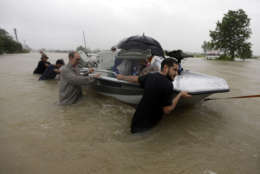 Evacuees are helped down Tidwell Road as floodwaters from Tropical Storm Harvey rise Monday, Aug. 28, 2017, in Houston. (AP Photo/David J. Phillip)