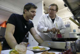 In this photo taken Tuesday, Dec. 3, 2013, CEO Josh Tetrick, left, watches as research and development chef Trevor Niekowal, right, makes a plant-based scrambled egg at Hampton Creek Foods in San Francisco.  Can plants replace eggs? A San Francisco startup backed by Bill Gates believes they can. Hampton Creek Foods is scouring the planet for plants that can replace chicken eggs in everything from cookies to omelets to French toast. Funded by prominent Silicon Valley investors, the upstart seeks to disrupt a global egg industry that backers say wastes energy, pollutes the environment, causes disease outbreaks and confines chickens to tiny spaces. (AP Photo/Eric Risberg)