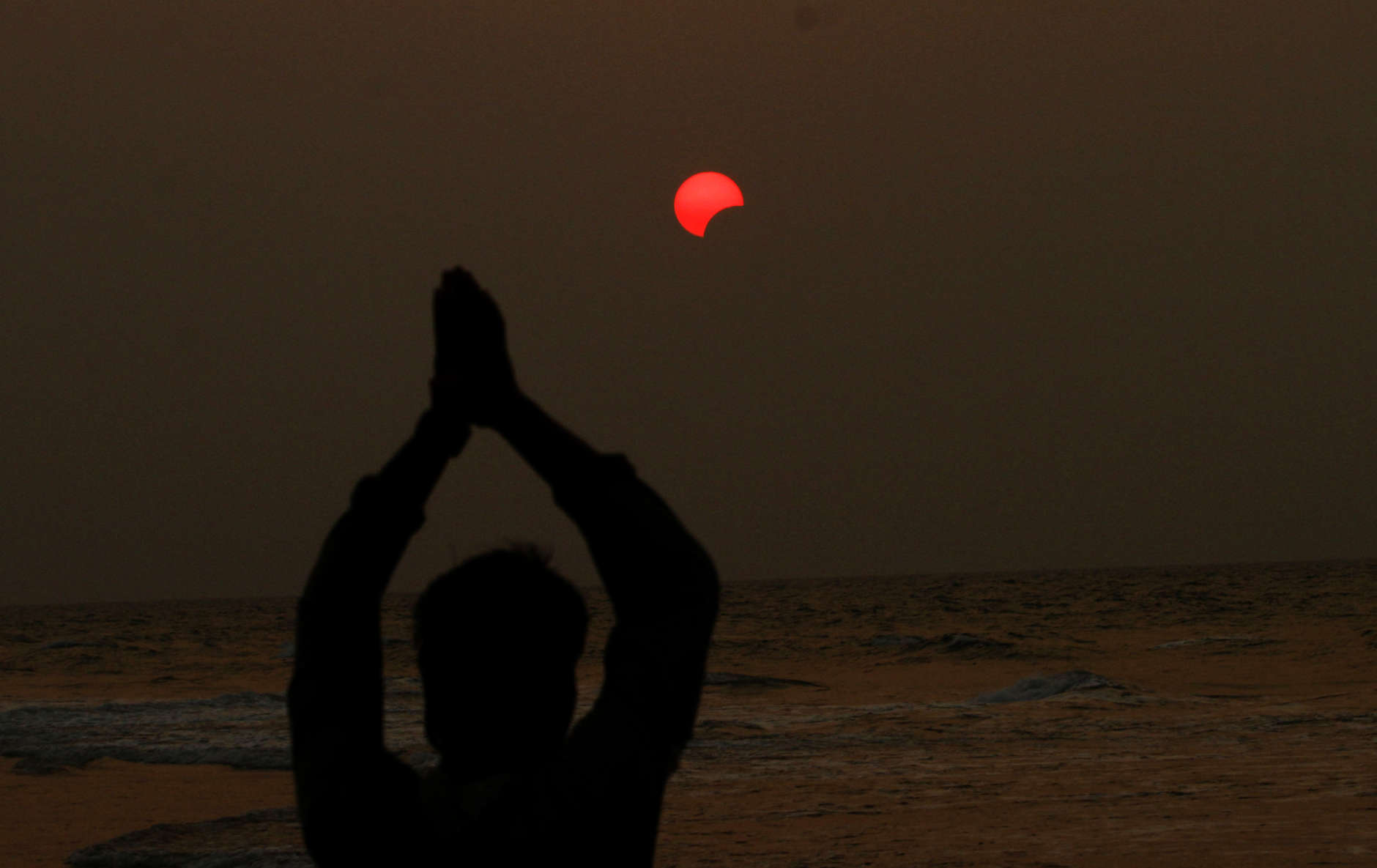 A fisherman prays during a partial solar eclipse in the sky over Bay of Bengal in Konark, 60 kilometers (37 miles) from the eastern Indian city Bhubaneswar, on Wednesday, March 9, 2016. (AP Photo/Biswaranjan Rout)