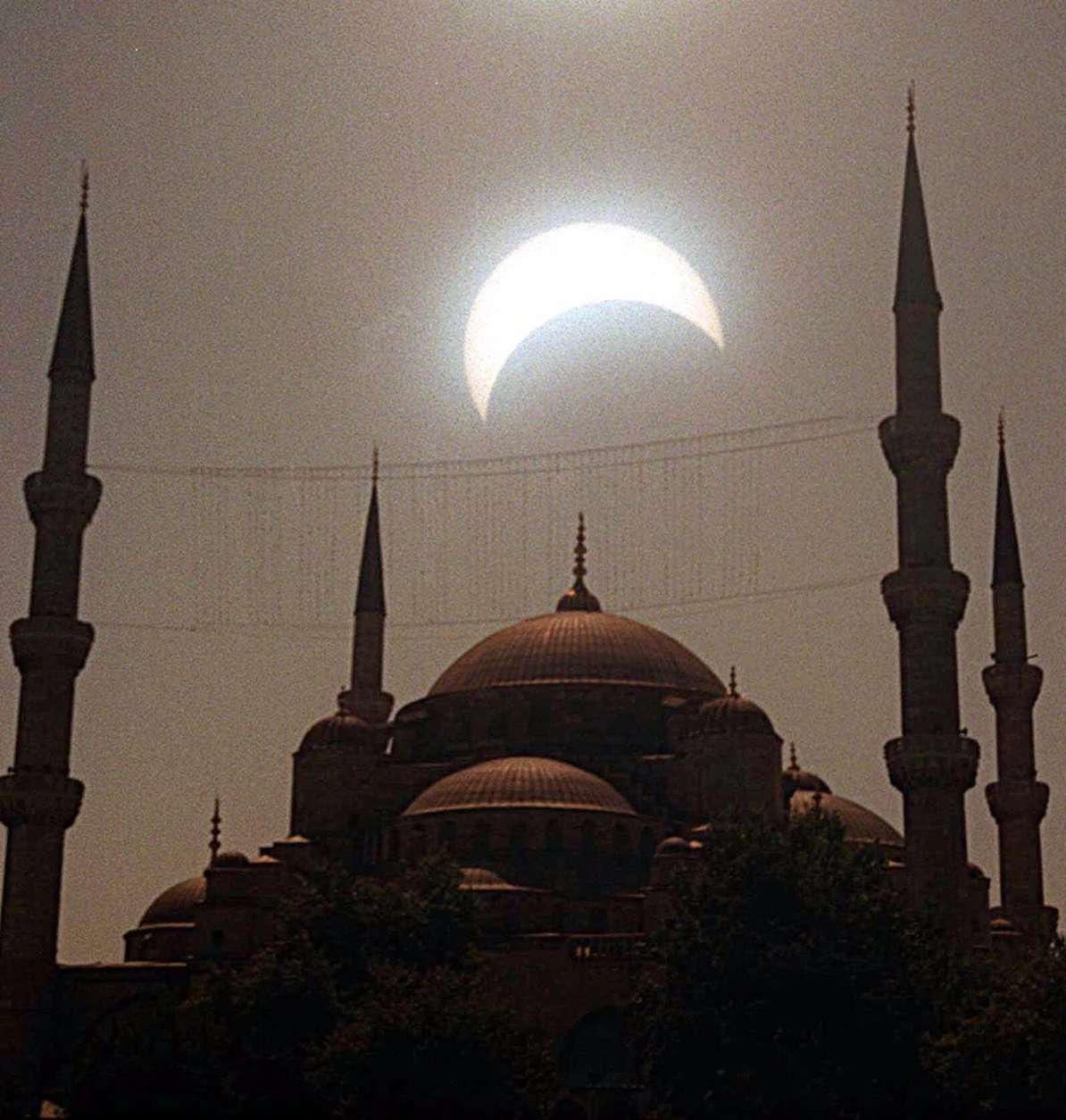 The solar eclipse is seen between the minarets of the historical Blue Mosque in Istanbul, Turkey on Wednesday August 11, 1999. This is the last solar eclipse of this millenium, which swept accross Europe towards the Bay of Bengal. (AP Photo/Erhan Sevenler/Anatolia)
