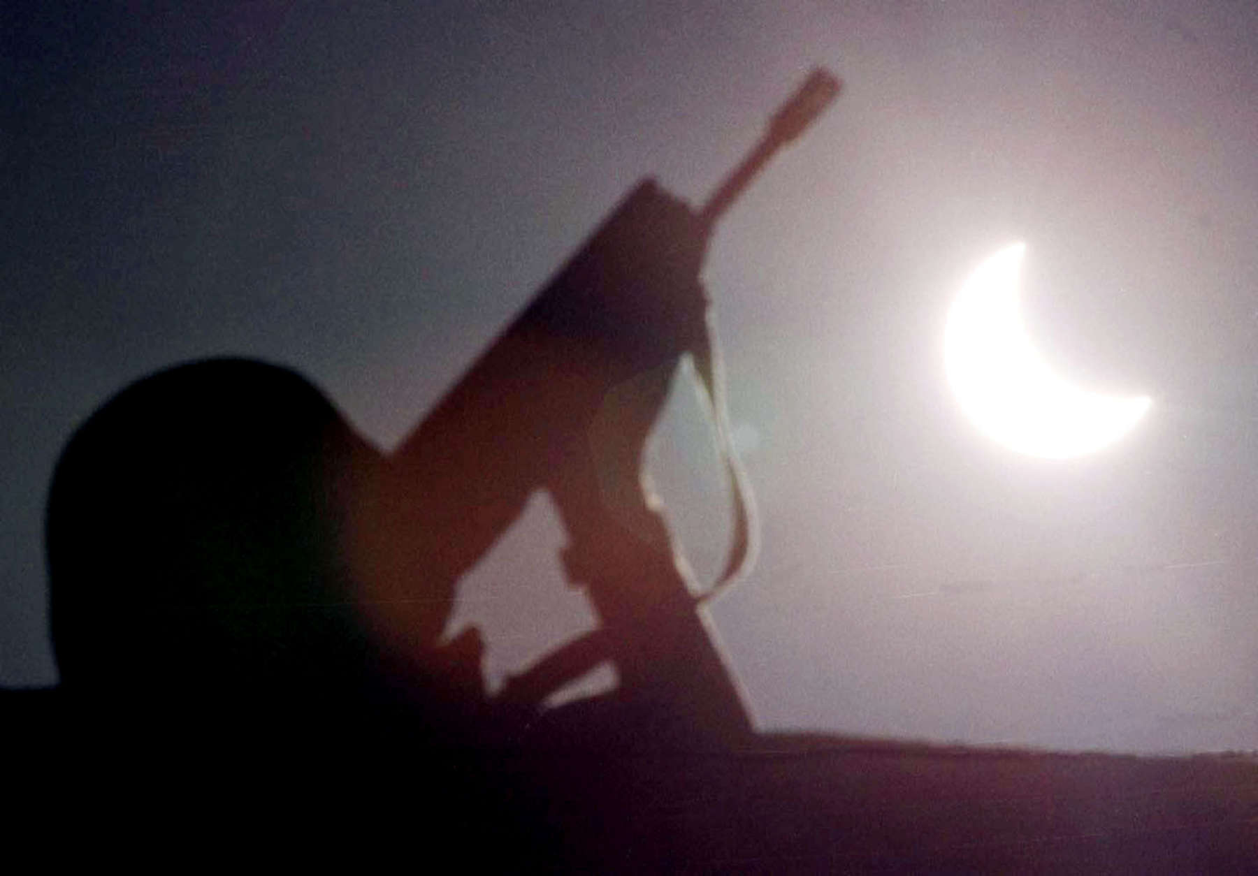 A French soldier, part of NATO's peacekeeping forces in Kosovo, stands guard beneath the solar eclipse on the ethnic Albanian side of the bridge dividing Kosovska Mitrovica, about 30 kilometers (20 miles) north of Pristina, Yugoslavia, Wednesday August 11, 1999. (AP Photo/Amel Emric)