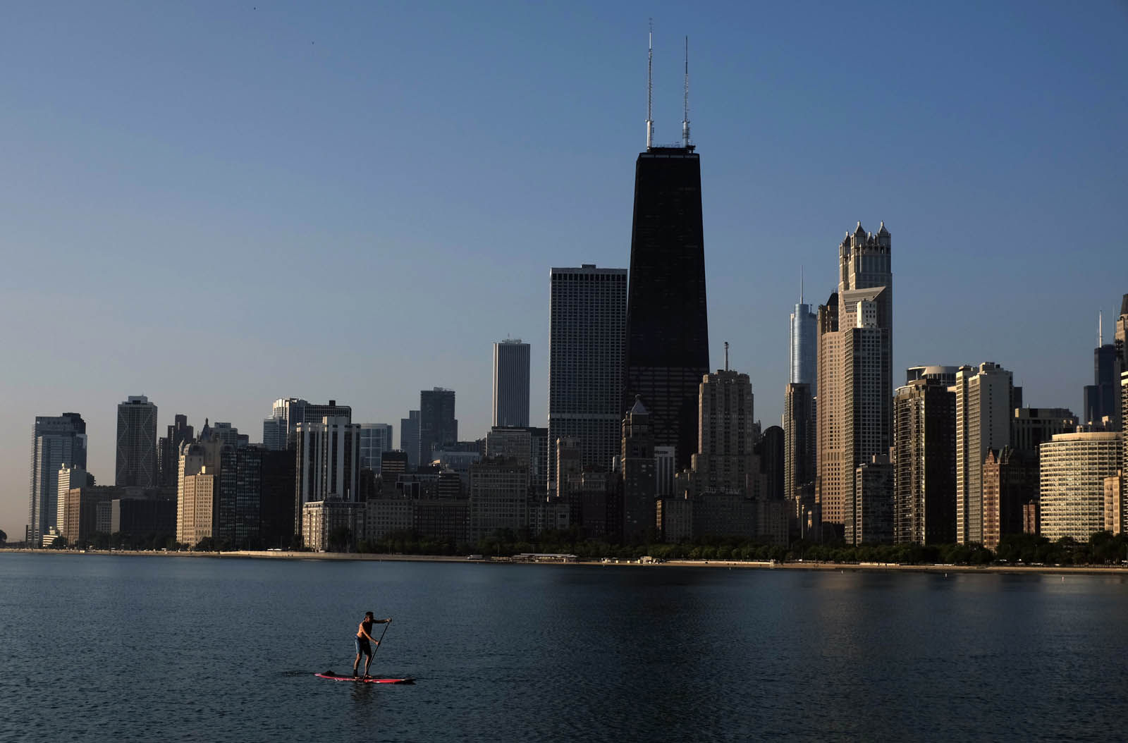 A paddle boarder coasts along the smooth surface of Lake Michigan with the downtown skyline in the background Wednesday morning, Aug. 20, 2014, in Chicago. (AP Photo/Kiichiro Sato)