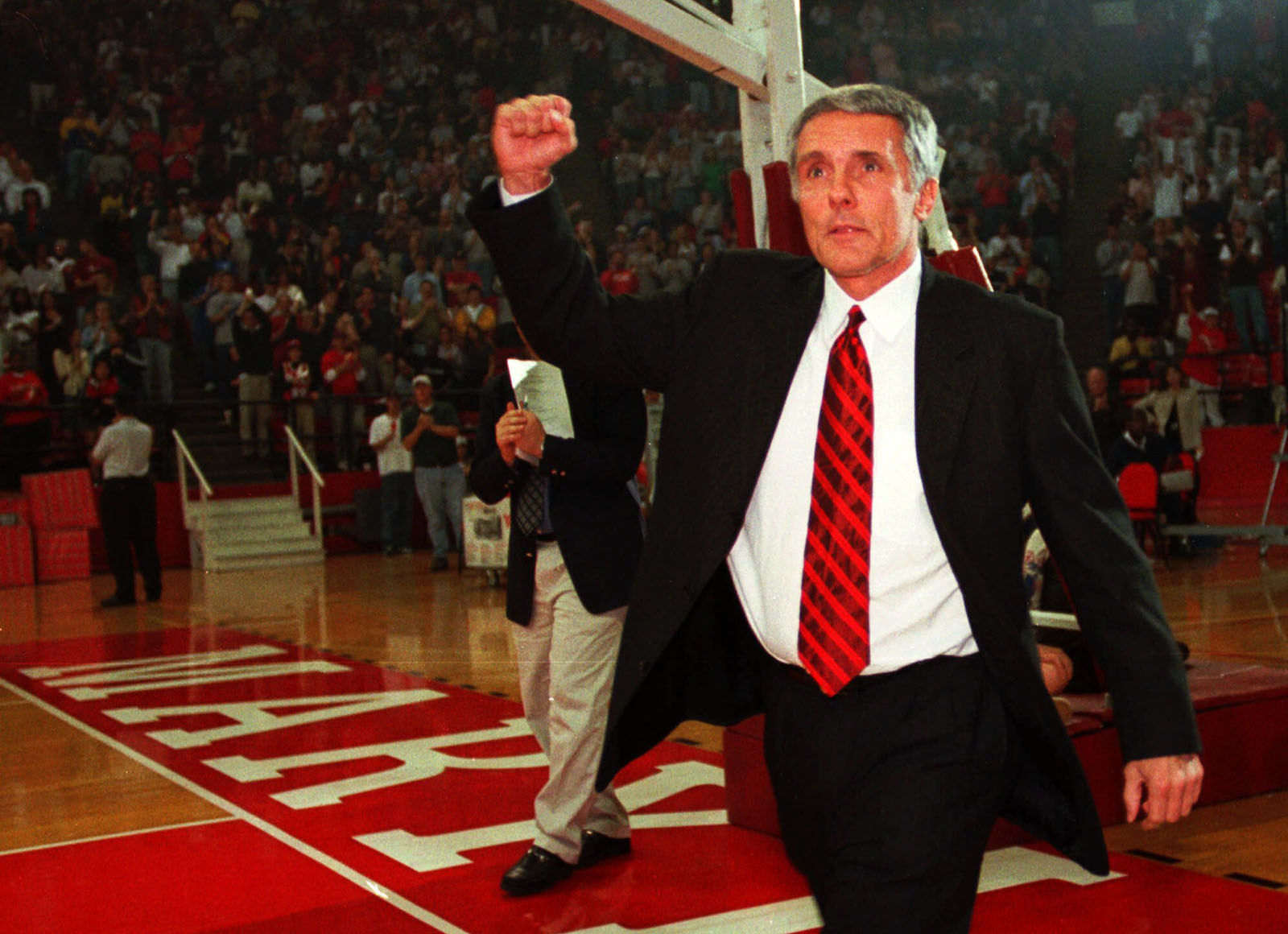Maryland basketball head coach Gary Williams pumps his fist to the Midnight Madness crowd, Saturday, Oct. 16, 1999, at Cole Field House in College Park, Md. Maryland held it's first practice of the season at midnight.(AP Photo/Nick Wass)
