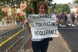"""Colleen Cook, 26, holds a sign as hundreds of people are facing off in Charlottesville, Va., ahead of a white nationalist rally planned in the Virginia city's downtown, Saturday, Aug. 12, 2017.   Cook, a teacher who attended UVA, said she sent her black son out of town for the weekend. """"This isn't how he should have to grow up,"""" she said. (AP Photo/Sarah Rankin)"""