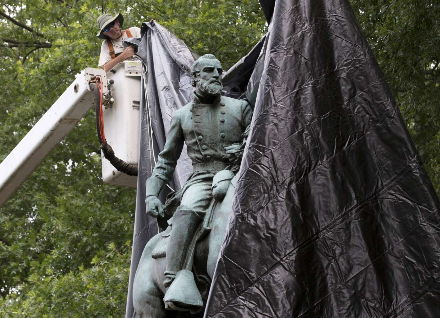 City workers drop a tarp over the statue of Confederate General Stonewall Jackson in Justice park in Charlottesville, Va., Wednesday, Aug. 23, 2017.  The move to cover the statues is intended to symbolize the city's mourning for Heather Heyer, killed while protesting a white nationalist rally earlier this month.  (AP Photo/Steve Helber)