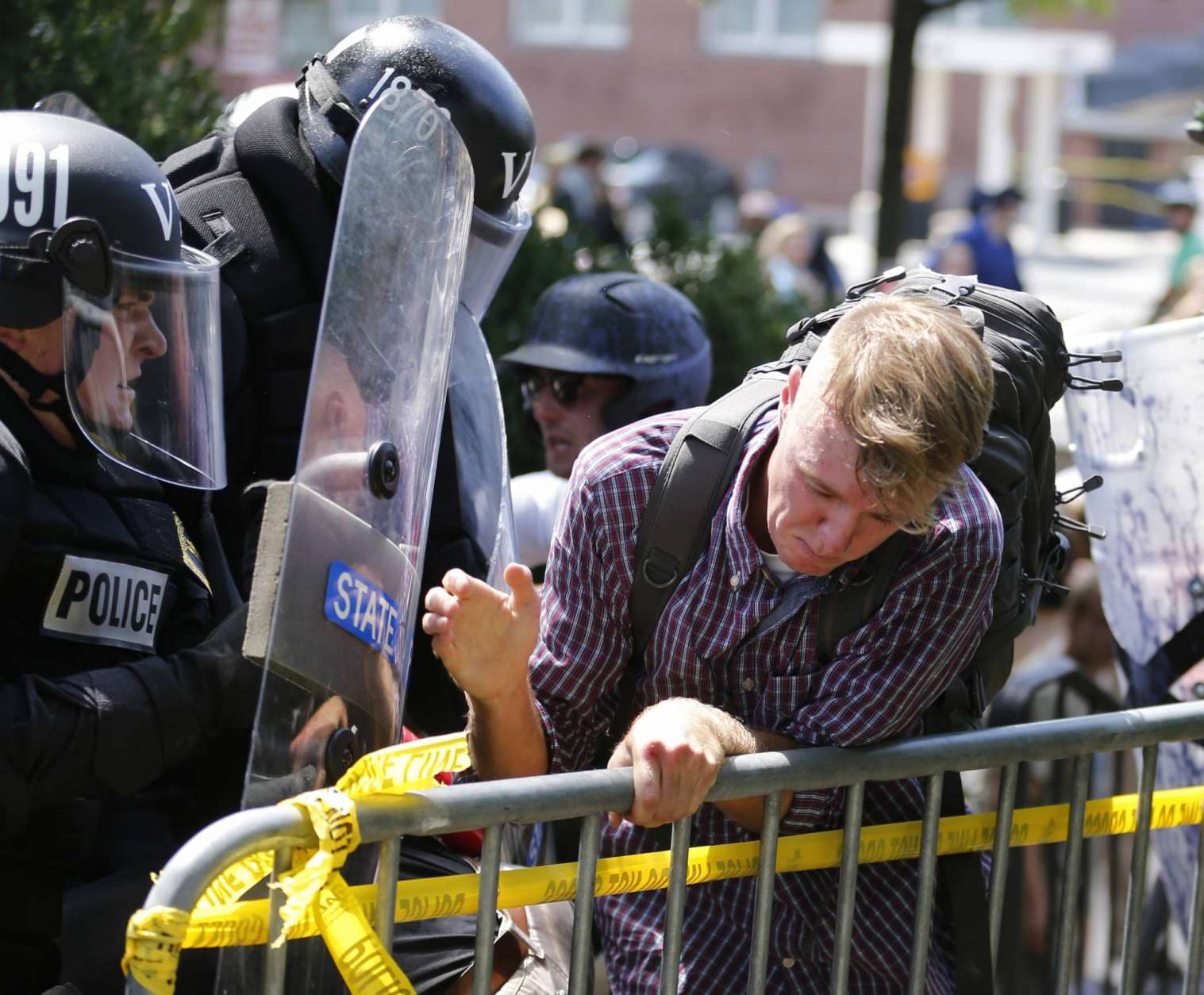 An white nationalist demonstrator is pushed out of the park by police at the entrance to Lee Park in Charlottesville, Va., Saturday, Aug. 12, 2017.  Gov. Terry McAuliffe declared a state of emergency and police dressed in riot gear ordered people to disperse after chaotic violent clashes between white nationalists and counter protestors. (AP Photo/Steve Helber)