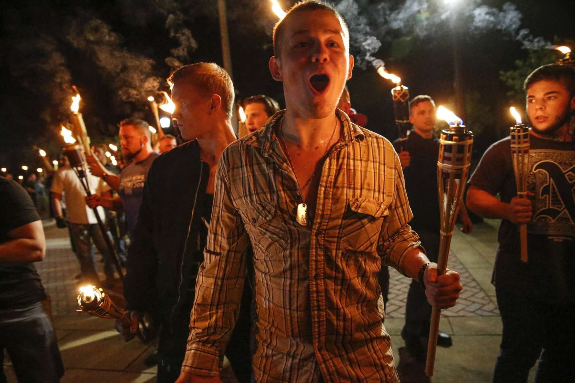 In this photo taken Friday, Aug. 11, 2017, multiple white nationalist groups march with torches through the UVA campus in Charlottesville, Va.   Hundreds of people chanted, threw punches, hurled water bottles and unleashed chemical sprays on each other after violence erupted at a white nationalist rally in Virginia. (Mykal McEldowney/The Indianapolis Star via AP)