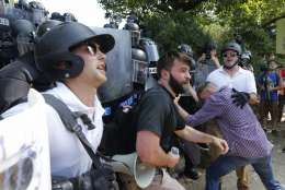 White nationalist demonstrators clash with police at the entrance to Lee Park in Charlottesville, Va., Saturday, Aug. 12, 2017.  Gov. Terry McAuliffe declared a state of emergency and police dressed in riot gear ordered people to disperse after chaotic violent clashes between white nationalists and counter protestors. (AP Photo/Steve Helber)