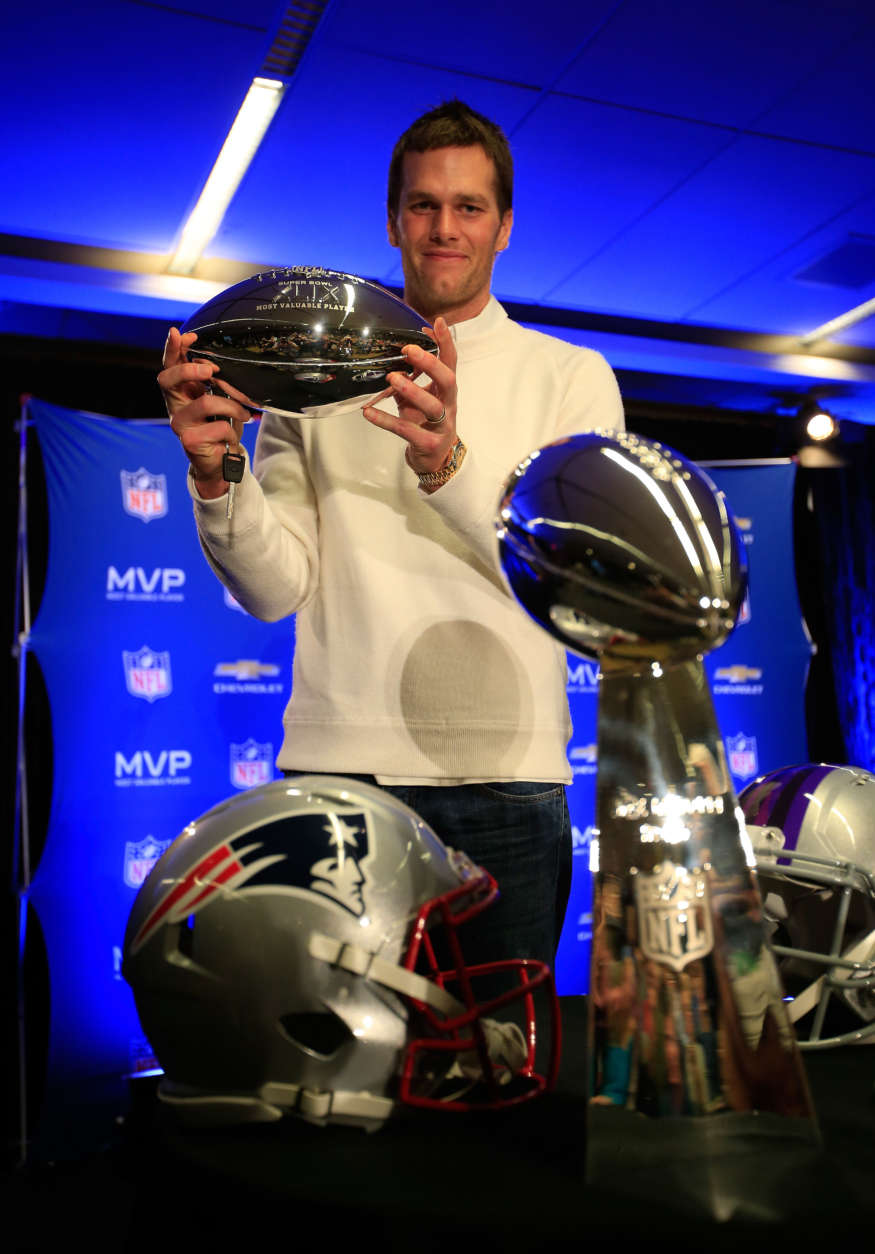 PHOENIX, AZ - FEBRUARY 02:  Tom Brady of the New England Patriots holds the Super Bowl XLIX MVP trophy during a Chevrolet Super Bowl XLIX MVP press conference following the Patriots Super Bowl win over the Seattle Seahawks on February 2, 2015 in Phoenix, Arizona.  (Photo by Jamie Squire/Getty Images)
